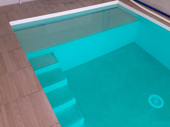 Construction piscine b ton rev tement quartz for Resine polyester piscine